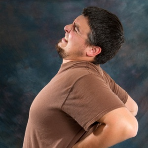 Picture of person holding their back with a link to the Symptoms we deal with page.